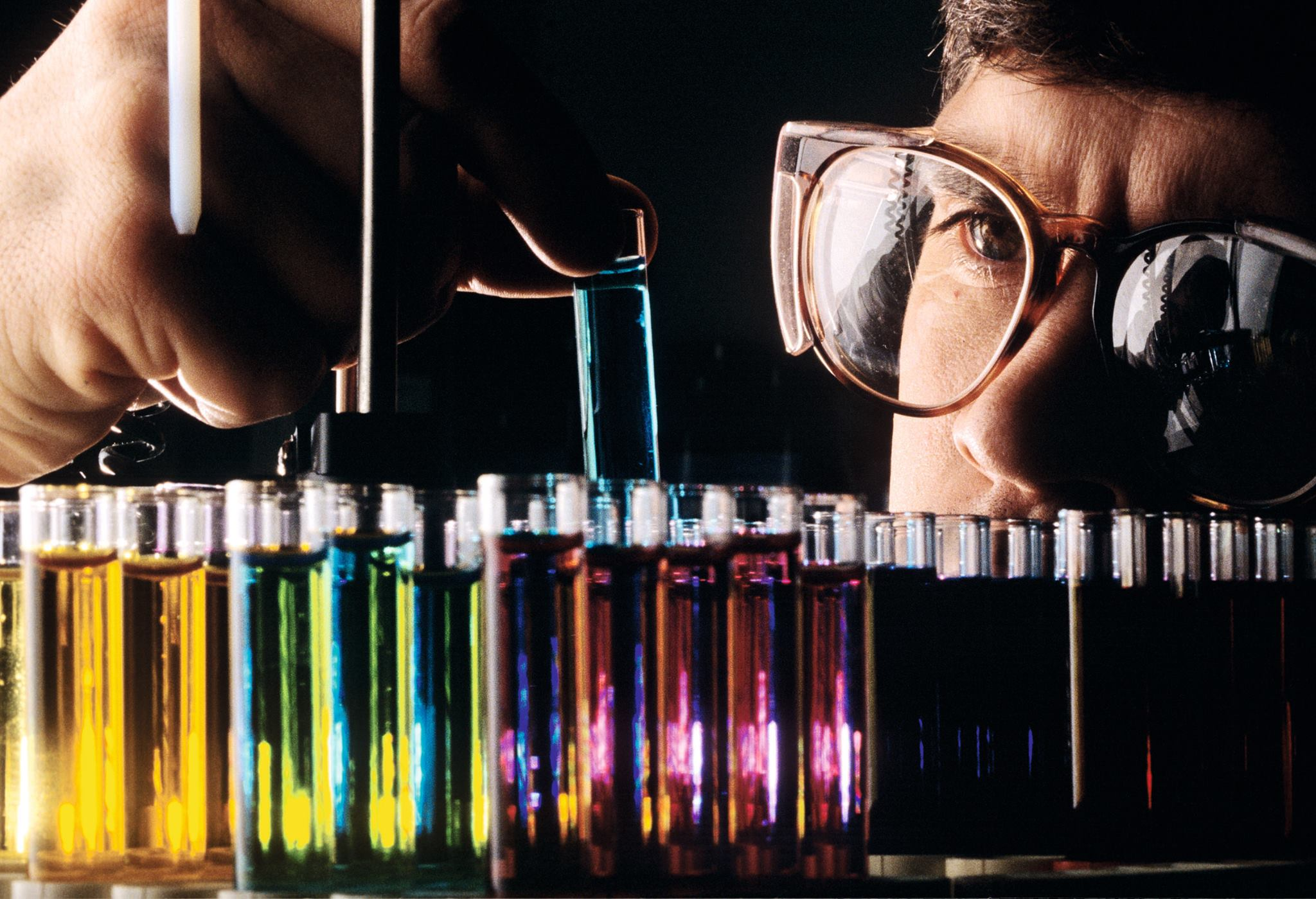 Scientist with color test tubes image