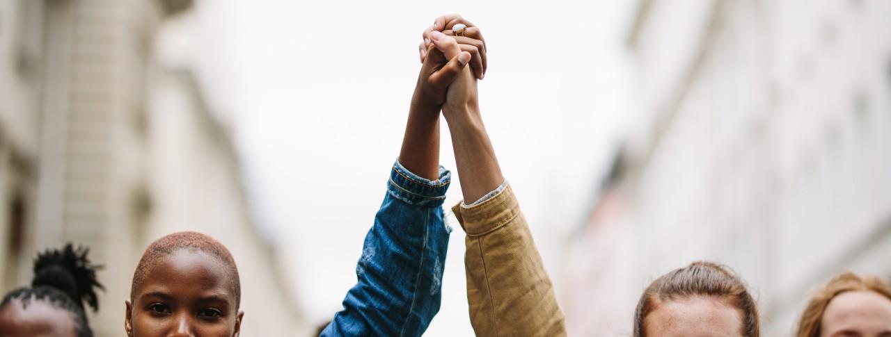 Dos mujeres cogiéndose de la mano en una manifestación en contra del racismo